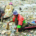 Indonesian men collect plastic rubbish for recycling on the Citarum river