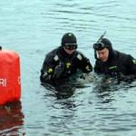 Tre sommozzatori si immergono a turno in un lago molto paludoso e melmoso.