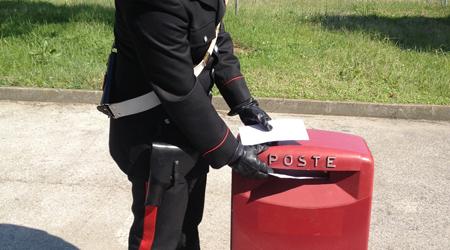 Un carabiniere si dirige verso la cassetta delle lettere,