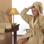 Una donna che si sta facendo la doccia finisce e si mette l'accappatoio